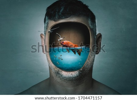 Surreal portrait of man with cropped face filled with water with a fish inside on a blue background. Surreal image. Surrealism. Royalty-Free Stock Photo #1704471157
