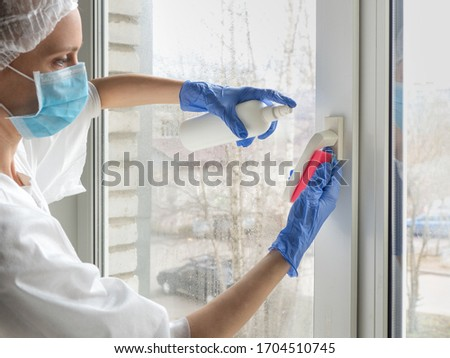 Coronavirus disinfection. People in making disinfection on windows. Doctor in rubber gloves disinfects windows handle with disinfectant and sponges. #1704510745