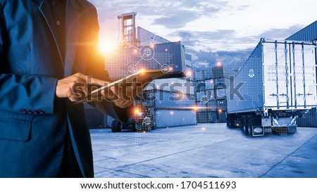 Global logistic or world of logistic concept. Businessman or manager using tablet standing with world map icon and shipping yard container and truck of transport background. fast or instant shipping. #1704511693