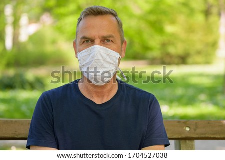 Middle-aged man wearing a surgical face mask in a head and shoulders portrait outdoors in a spring park during the coronavirus or Covid-19 pandemic #1704527038
