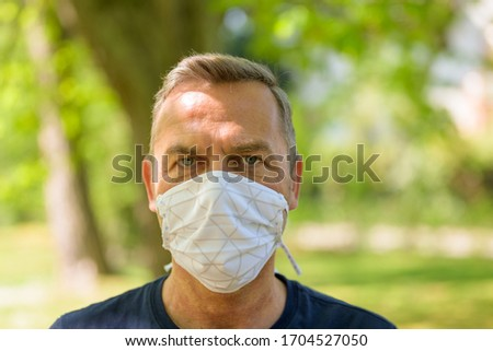 Head shot of a man wearing a surgical face mask outdoors in a park to prevent infection during the coronavirus or Covid-19 pandemic #1704527050