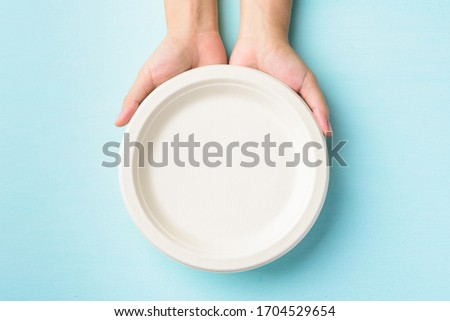 Biodegradable plate, Compostable plate or Eco friendly disposable plate holding by hand on pastel color background #1704529654