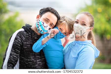 Family members embracing each other, smiling in the camera wearing cloth face masks. Many countries recommend citizens cover their faces during the world coronavirus covid-19 pandemic. Royalty-Free Stock Photo #1704532372