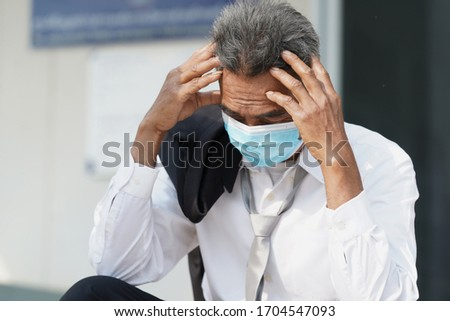 Unemployed man,Desperate businessman sitting hopelessly on stair in central business district due to unemployment from the COVID 19 disease situation,Coronavirus has turned into a global emergency. Royalty-Free Stock Photo #1704547093