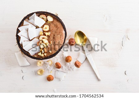 top view trendy chocolate smoothie bowl with frozen banana, coconut flakes, hazelnuts in coconut bowl with spoon on white background