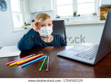 Coronavirus Outbreak. Lockdown and school closures. School boy with face mask watching online education classes feeling bored and depressed at home. COVID-19 pandemic forces children online learning. #1704582529