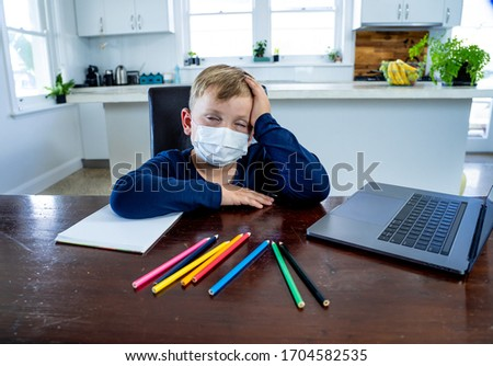 Coronavirus Outbreak. Lockdown and school closures. School boy with face mask watching online education classes feeling bored and depressed at home. COVID-19 pandemic forces children online learning. #1704582535