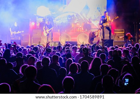Silhouettes of people enjoying live concert of musician band performing song on stage in bright spotlights Royalty-Free Stock Photo #1704589891