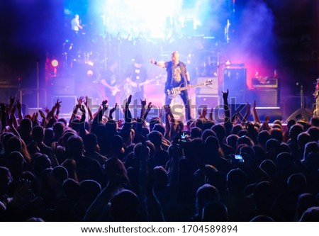 Fans at live rock music concert cheering musicians on stage, back view Royalty-Free Stock Photo #1704589894