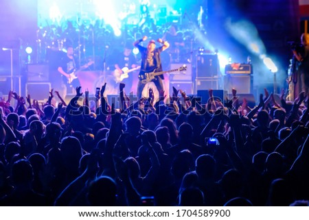 Fans at live rock music concert cheering musicians on stage, back view Royalty-Free Stock Photo #1704589900