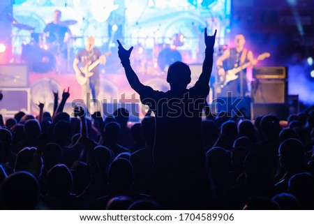 Fans at live rock music concert cheering musicians on stage, back view Royalty-Free Stock Photo #1704589906