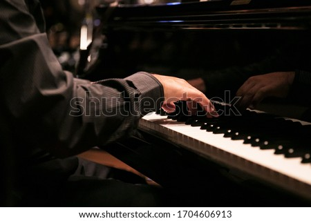 Close-up of a  hand playing the piano