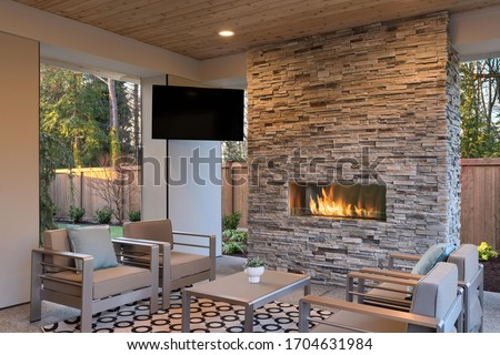 Luxury outdoor relaxing living room with large stone fireplace, TV, rug and beige sofa.  Royalty-Free Stock Photo #1704631984