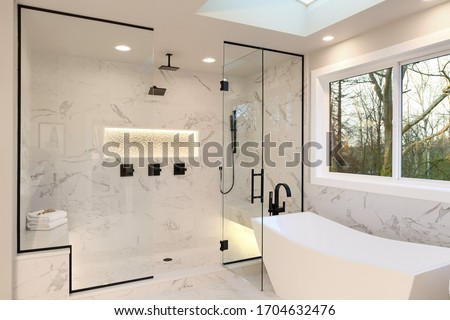 Detailes of the larhe walk in shower with white marble and mosaic, light. Three handles, shower head in dark brass.and free standing modern tub. Royalty-Free Stock Photo #1704632476