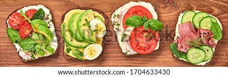 Open sandwiches with avocado, tomato, mozzarella and soft cheese. Homemade sandwich with ham, cucumber, radish sprouts on wooden board. Top view, sandwich closeup, banner #1704633430