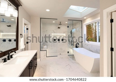 Luxury modern home bathroom interior with dark brown cabinets, white marble, walk in shower, free standing tub, two mirrors, flowers. #1704640822