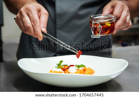 Chef hand cooking pasta penne with mozzarella cheeze and sun-dried tomatoes in a white plate, horizontal format #1704657445