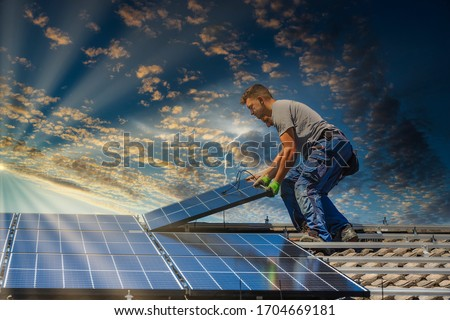 Installing solar photovoltaic panel system. Solar panel technician installing solar panels on roof. Alternative energy ecological concept.  Royalty-Free Stock Photo #1704669181