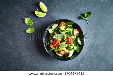 Avocado, tomato and cucumber salad with fresh herbs on dark stone background. Healthy summertime salad. Copy space #1704675412