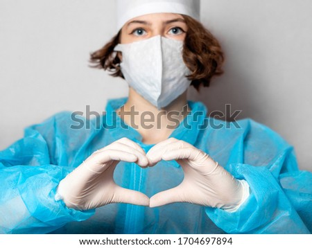 Medical worker in a disposable mask and a lab coat makes a heart sign. Gray homogeneous background. Conceptual photo: doctors on the protection of health, with love for people.
