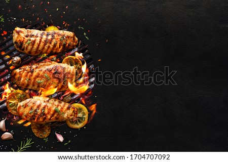 Grilled chicken breasts on a grill plate on black background with copy space, top view. Bbq background Royalty-Free Stock Photo #1704707092