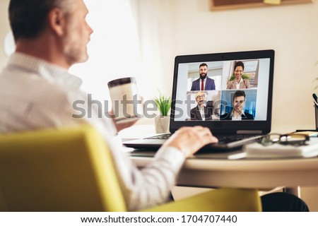 Man working from home having online group videoconference on laptop #1704707440