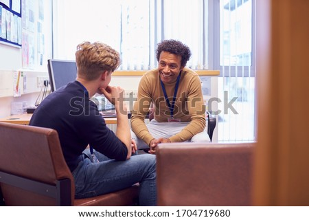 Male College Student Meeting With Campus Counselor Discussing Mental Health Issues Royalty-Free Stock Photo #1704719680