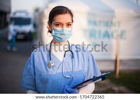 Portrait of overworked stressed worried UK NHS ICU doctor in front of EMS hospital,Emergency Medical Services frontliner,COVID-19 pandemic outbreak crisis,key worker medical staff working long shifts  #1704722365