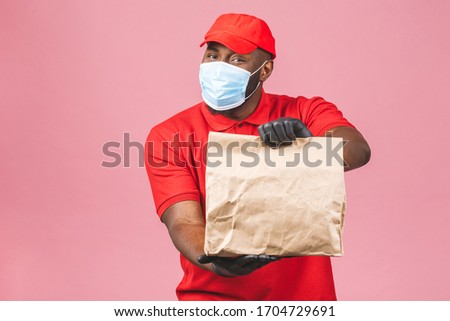 Delivery african american man employee in red cap blank t-shirt uniform face mask gloves hold empty cardboard box isolated on pink background. Service quarantine pandemic coronavirus virus 2019-ncov.  #1704729691