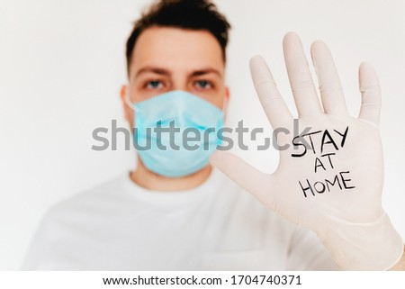 Stop Corona virus! A young european man in mask and gloves with sign Stay at home. Covid-19 protection #1704740371