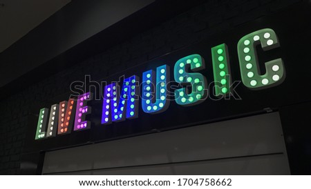 led Neon shining signboard at night.Led - Neon inscription of Live Music.