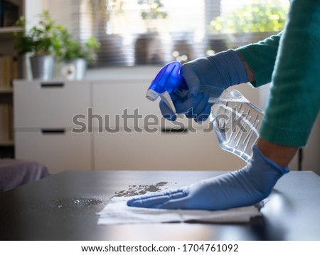 surface home cleaning spraying antibacterial sanitizing spray bottle disinfecting against COVID-19 spreading wearing medical blue gloves. Sanitize surfaces prevention in hospitals and public spaces. Royalty-Free Stock Photo #1704761092