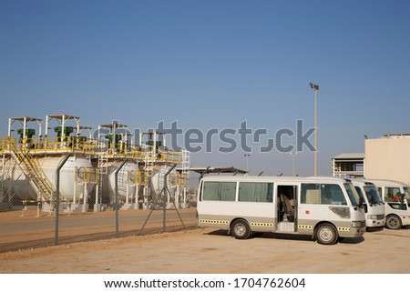 Several buses transporting immigrant workers parked next to an oil production station in Middle East country #1704762604