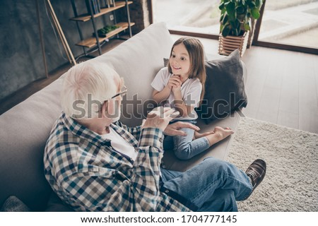 Photo of funny two people old grandpa little interested granddaughter sitting sofa telling good story stay house quarantine safety modern design interior living room indoors Royalty-Free Stock Photo #1704777145