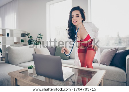 You turn me on babe. Photo of tempting slim lady work home online notebook chat passion naughty nurse role listen stethoscope heart beating lab coat look screen wear red bikini tights indoors