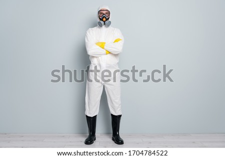 Full body photo of professional guy disinfectant watch public places disinfection arms crossed wear white hazmat protective suit goggles mask gloves gumboots isolated grey color background Royalty-Free Stock Photo #1704784522