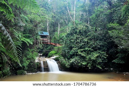 A picture of waterfall with green rain forest in the background and an old bridge with a hut in the middle of the bridge. Photo of waterfall with slow shutter effect.