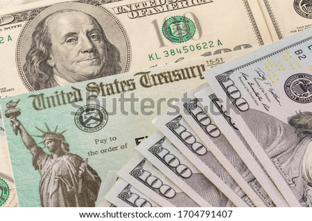 Stack of 100 dollar bills with illustrative coronavirus stimulus payment check to show the virus stimulus payment to Americans Royalty-Free Stock Photo #1704791407