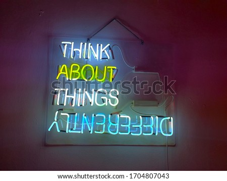 Neon sign phrase 'Think about things different'. A glowing neon sign that is often used in shop interior design.