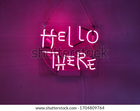 Neon sign phrase 'Hello there'. A glowing neon sign that is often used in shop interior design.
