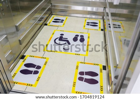 View of footprint sign for stand in lift. Social distancing with COVID-19 coronavirus crisis.yellow footprint sign with text caution social distance, Social distancing the elevator (Lift) in hospital.