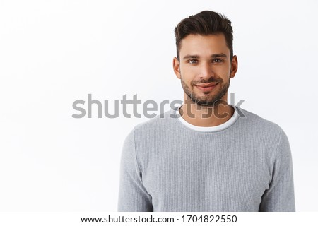 Close-up happy smiling confident macho man with bristle in stylish grey sweater, looking trustworthy and sincere with friendly kind grin, standing white background self-assured and motivated #1704822550