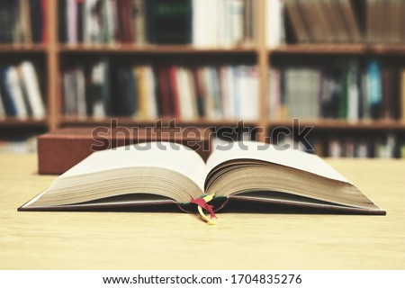 Open book on the table in library #1704835276