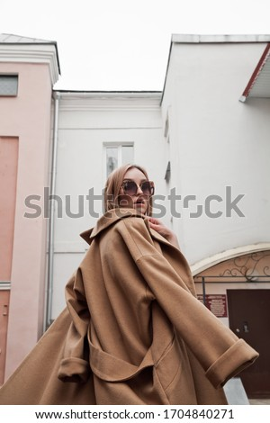 Ultra-fashion concept. Girl model in fashionable clothes. Fashion photo. Luxury clothes, street style.A stylish total beige look. Model is spinning around in a coat. Image in motion