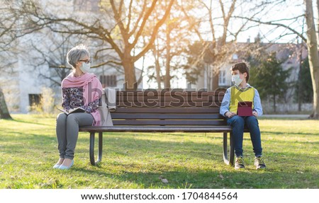 Grandmother and grandson separated by social distancing on park bench #1704844564