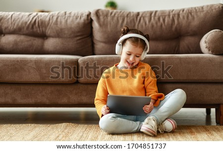 Full body cheerful girl in casual clothes and headphones smiling and playing game on tablet while sitting on soft couch at home