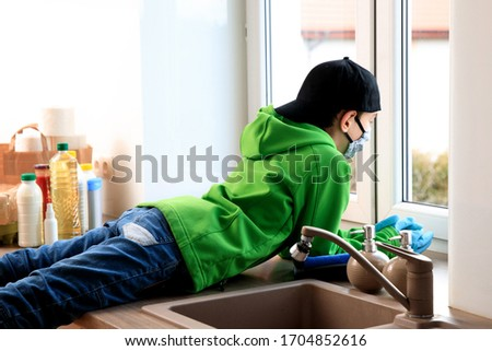 the boy wears a medical mask. A child sitting by the window and looking outside. he looks bored and sad. He may get sick or quarantined because of Coronavirus 19 #1704852616
