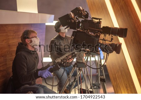 masked cameraman is filming a television show in the studio. TV #1704922543