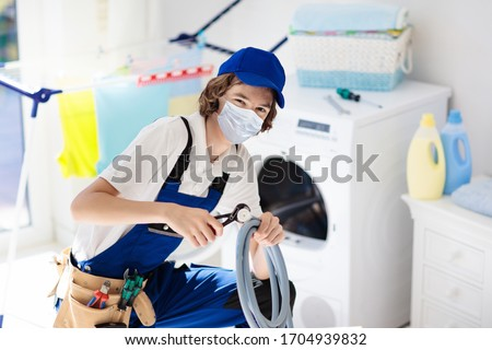 Plumber emergency service during coronavirus outbreak. Technician in face mask repairing broken washer. Maintenance of home and household appliance in lockdown and quarantine. Urgent repair. #1704939832