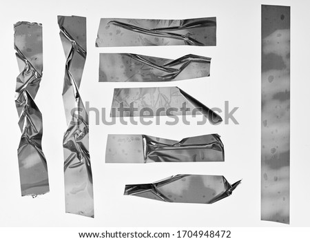 Metallic sticky teared tape shapes cuts isolated on white background. Shiny flexible crumpled glitter holo stickers. Silver metallic stripes, adhesive pieces. Design elements for a poster idea. #1704948472